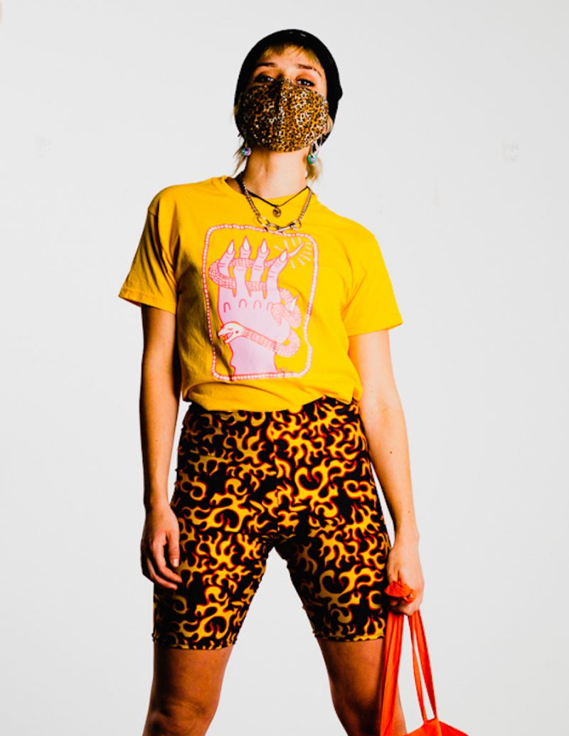 person wearing yellow top with pink print of hand